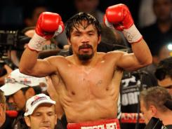 Manny Pacquiao celebrates his majority decision victory against Juan Manuel Marquez to retain his WBO welterweight title.