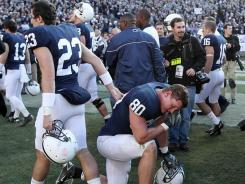 Penn State's Andrew Szczerba, No. 80, takes a moment to reflect as Ryan Keiser, No. 23, walks past in the emotional aftermath of Saturday's loss to Nebraska.