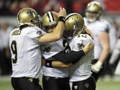 Saints K John Kasay is mobbed by QBs Drew Brees (9) and Chase Daniel (10) after his game-winning OT kick in Atlanta on Sunday.