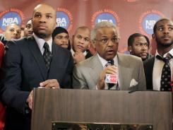 Surrounded by NBA players, NBPA executive director Billy Hunter (holding microphone) and NBPA president Derek Fisher speak to the media after the players rejected the league's latest offer.