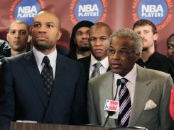 Surrounded by NBA players, union president Derek Fisher, left, and executive director Billy Hunter talk to reporters. The NBA players rejected the league's latest offer.