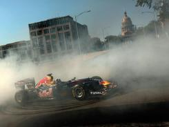 Formula One driver David Coulthard of Great Britain completes a burnout while driving a show car in front of the Texas Capitol building in August during a promotional stop for the circuit's scheduled 2012 race.