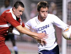 Louisville defender Austin Berry, left, battles Connecticut defender Sean Weir for the ball during a regular-season matchup.