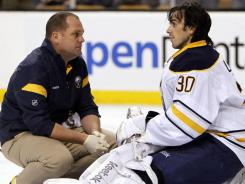 Buffalo Sabres goalie Ryan Miller is tended to by the trainer after being charged by Boston Bruins left wing Milan Lucic Saturday.