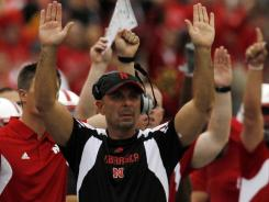 Carl Pelini signals to players Sept. 3 for Nebraska, a school that has removed academically related bonus provisions from its coaches' contracts.