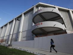 A person walks past Syracuse's Carrier Dome Friday. The arena is home to the Orange basketball program.