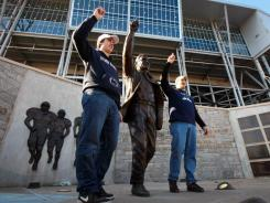 Penn State alumni Tommy Nicchi, right, and his brother Tony get their picture taken next to Joe Paterno's statue before last weekend's game between Penn State and Nebraska Saturday, Nov. 12, 2011 in State College, Pa.