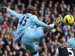 Manchester City's Mario Balotelli beats Newcastle's Danny Simpson to the ball during their Saturday English Premier League tilt.