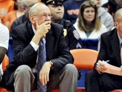 Syracuse head coach Jim Boeheim watches the game beside the empty chair of associate head coach Bernie Fine during the first half of an NCAA college basketball game against Colgate in Syracuse, N.Y., Saturday, Nov. 19, 2011.