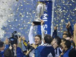 David Beckham, hoisting the Major League Soccer championship trophy Sunday after the Galaxy defeated the Dynamo 1-0, dismissed speculation that he'll play in France next year.