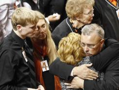 Oklahoma State interim coach Jim Littell, right, hugs Shelley Budke, wife of Kurt Budke, on Monday. At left are two of the Budkes' three children.