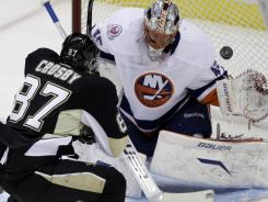 Pittsburgh Penguins' Sidney Crosby scores a first-period goal over New York Islanders goalie Anders Nilsson on Monday in his first game back from a concussion.