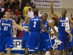 Memphis teammates Preston Laird (31), Antonio Barton (2), Trey Draper, right center, and Stan Simpson (32) rejoice after their double overtime win against Tennessee.