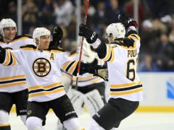 The Bruins' Benoit Pouliot (67) celebrates his shootout-winning goal against the Sabres with his teammates Wednesday. Boston notched its 10th consecutive win, a feat it hasn't reached since the end of 2008.