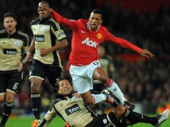 Manchester United midfielder Nani is tackled by Benfica's Ezequiel Garay during the second half of their Champions League draw.