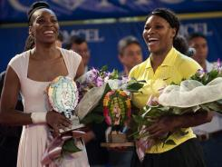 Venus and Serena Williams share a laugh after playing an exhibition match in Colombia on Wednesday.