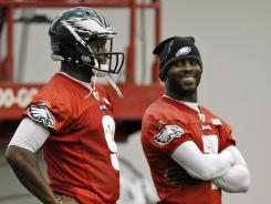 Eagles quarterback Vince Young, left, stands as quarterback Michael Vick smiles during Wednesday's practice in Philadelphia.
