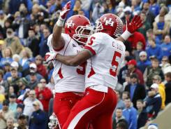 Houston's Justin Johnson, left, and Charles Sims celebrate a touchdown by the latter during the second quarter of their 48-16 victory over Tulsa.