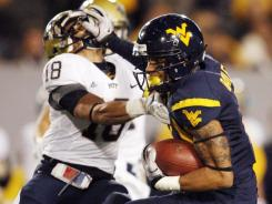 West Virginia receiver Stedman Bailey (right) stiff-armed his way past Jarred Holley (18) en route to a 63-yard touchdown catch in the second quarter.