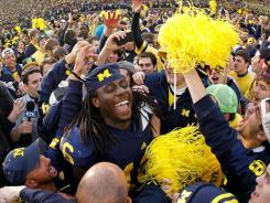 Michigan quarterback Denard Robinson fans after the Wolverines beat Ohio State for the first time since 2003.