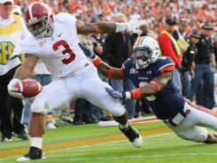 Alabama running back Trent Richardson gets by Auburn  defensive back Jonathon Mincy  for a touchdown in the first half.