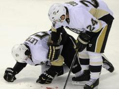 Pittsburgh Penguins defenseman Kris Letang, left, is tended to by teammate Matt Cooke after being hit by Montreal Canadiens' Max Pacioretty Saturday.