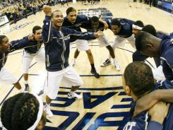 Pitt's Nick Rivers, center,  gets the Panthers fired up before their 81-71 victory against Robert Morris.