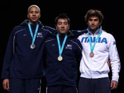 Silver medal winner Miles Chamley-Watson, left, Gerek Meinhardt (gold medal winner) and Italy's Tommaso Lari  who won bronze, pose on the podium after the men's foil competition at the Fencing Invitational, a test event for the 2012 London Olympics.