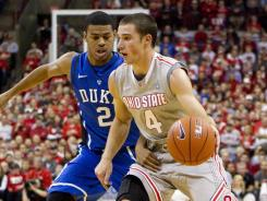Ohio State guard Aaron Craft (4) drives past Duke Blue Devils forward Quinn Cook (5) at Value City Arena in Columbus, Ohio on Tuesday.
