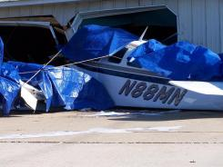 The wreckage of a plane crash is seen on Saturday, June 25, 2011 in Charlevoix, Mich. The single-engine plane that took off from eastern Indiana crashed into a garage in a neighborhood near a northwestern Michigan airport, leaving two people dead and another person injured, federal officials said.