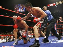 Miguel Cotto, left, is knocked down by Antonio Margarito during the 11th round of their WBA welterweight championship match on July 26, 2008. Margarito won by TKO.