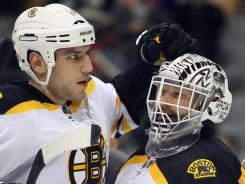 Milan Lucic, left, celebrates the Bruins' win with goalie Tim Thomas. Lucic scored two goals, the second serving as critical insurance with less than five minutes to play.