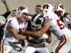 Michigan State's Keith Nichol, center, pushes through two Wisconsin defenders.