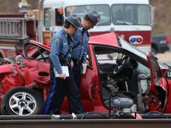Missouri Highway Patrol officers inspect the scene of a fatal train-car collision at the intersection of U.S. 59 highway and highway 45 near Rushville, in southern Buchanan County Monday morning, Nov. 21, 2011. (AP Photo/St. Joseph News-Press, Eric Keith)