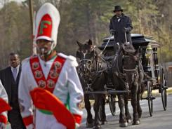 A horse drawn carriage carrying the casket of Florida A&M University band member Robert Champion is lead by his fellow band members following his funeral service Wednesday, Nov. 30, 2011 in Decatur, Ga. The 26-year-old was found dead on Nov. 19 on a bus parked outside an Orlando, Fla. hotel after the school's football team lost to a rival. Authorities suspect hazing but have not released any further details.