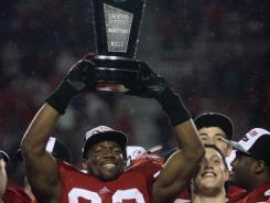 Badgers lineman Louis Nzegwu (93) hoists the Legends division championship trophy after the game against the Penn State Nittany Lions at Camp Randall Stadium.