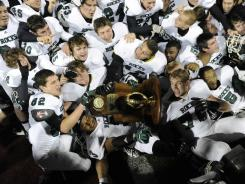 Trinity players celebrate their 62-21 win over Scott County in the KHSAA 6-A state title game. The No. 2 Shamrocks finished the season 14-0.