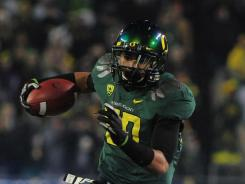 Oregon wide receiver Lavasier Tuinei runs for a first downl past UCLA safety Stan McKay during the third quarter of the Pac-12 Championship game at Autzen Stadium in Eugene, Ore.