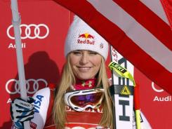 Lindsey Vonn waves an American flag on the podium after her first-place finish at the women's World Cup downhill race in Lake Louise, Alberta.