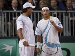 Eduardo Schwank and David Nalbandian of Argentina discuss strategy Saturday on their way to victory against Fernando Verdasco and Feliciano Lopez of Spain.