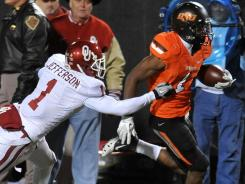 Oklahoma State running back Joseph Randle tries to outrun the tackle of Oklahoma's Tony Jefferson during the first half.