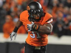 Oklahoma State running back Jeremy Smith is tackled by Oklahoma's Tony Jefferson on Saturday night during his 119-yard effort in the Cowboys' 44-10 victory.