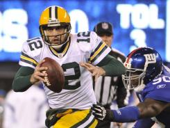 Green Bay Packers quarterback Aaron Rodgers scrambles under pressure from New York Giants defensive end Jason Pierre-Paul. Rodgers tossed 369 yards and four touchdowns in the Packers' win.