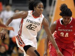Miami's Shenise Johnson (42) drives past Rutgers' Monique Oliver during their matchup on Monday in Coral Gables, Fla. Johnson had a double-double, scoring 25 points and hauling in 12 rebounds, in Miami's 92-81 win in double overtime.