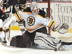 Bruins goalie Tim Thomas makes a kick save in the first period. Thomas stopped 45 shots as the Bruins improved to 14-0-1 in their last 15 games.