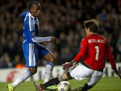 Chelsea's Ivorian forward Didier Drogba (L) slots the ball past Valencia's goalkeeper Diego Alves (R) to score the third goal during their UEFA Champions League group E football match at Stamford Bridge, London, on December 6, 2011. Chelsea won the game 3-0.