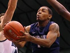 Xavier guard Mark Lyons (center) drives to the hoop between two Butler defenders during the first half at Hinkle Fieldhouse in Indianapolis.