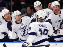 Dominic Moore, whose errant practice shot hit Martin St. Louis in the face and ended St. Louis's 499 consecutive games streak, scored the game-tying and game-winning goal for the Lightning.