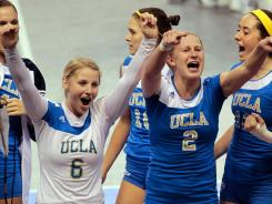 UCLA's Lainey Gera (6), Kelly Reeves (2) and several of their teammates celebrate after defeating Penn State during an NCAA regional semifinal volleyball match. Penn State had won the last four national titles before the loss.