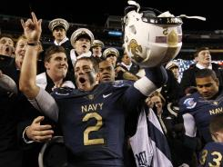 Navy quarterback Kriss Proctor, center, celebrates with Midshipmen after beating Army 27-21 on Saturday in Landover, Md.